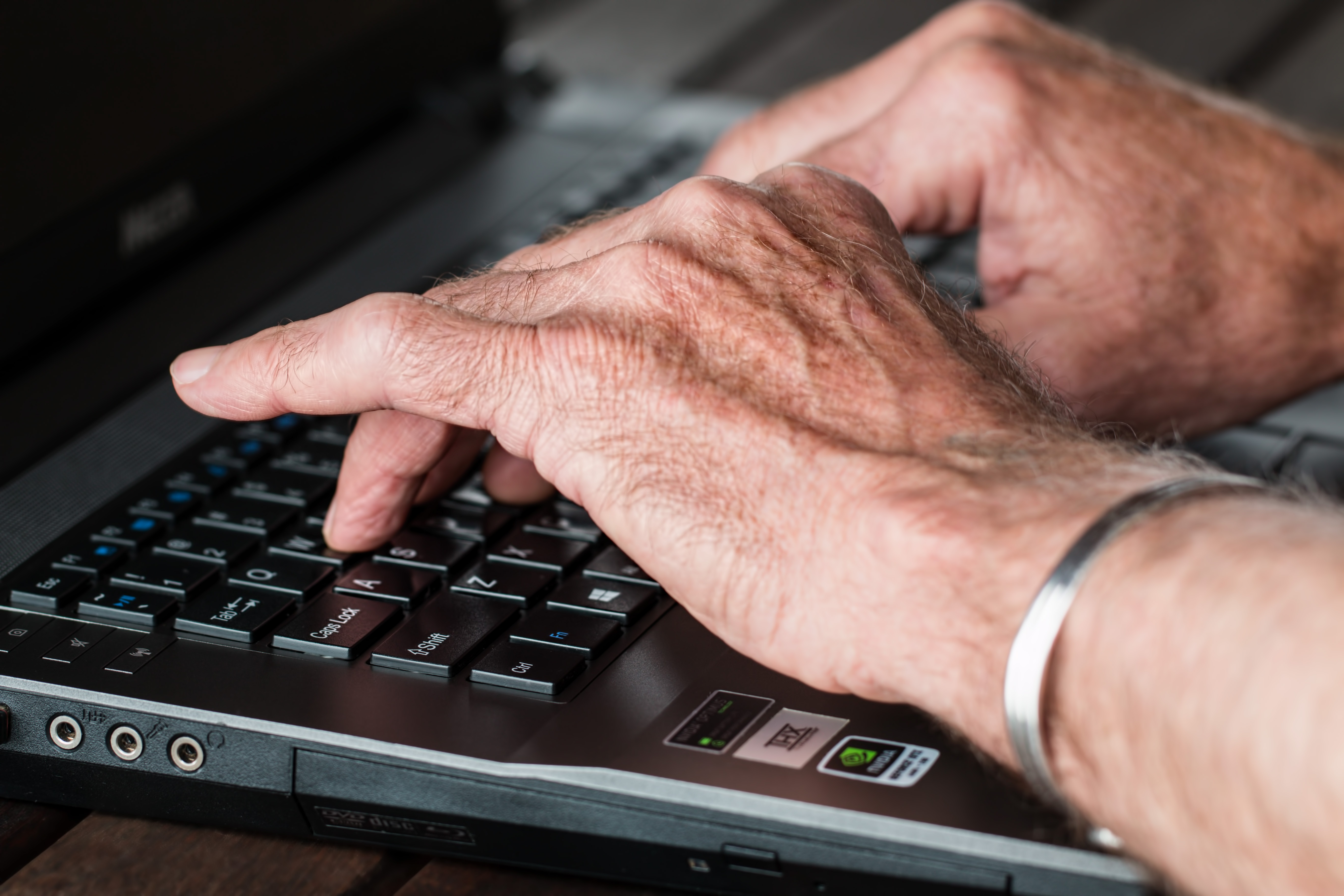 picture of elderly hands typing on a laptop